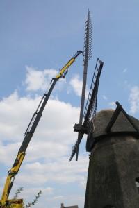 En vinge hejses op af kranen. Den skal føres ned gennem navet, hvorefter den færdigmonteres.